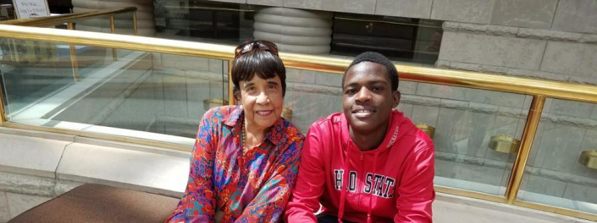 Dr. Faye Gary and Provost Scholar sitting on a bench at the museum