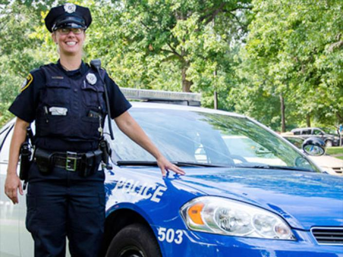 Female officer standing by patrol vehicle