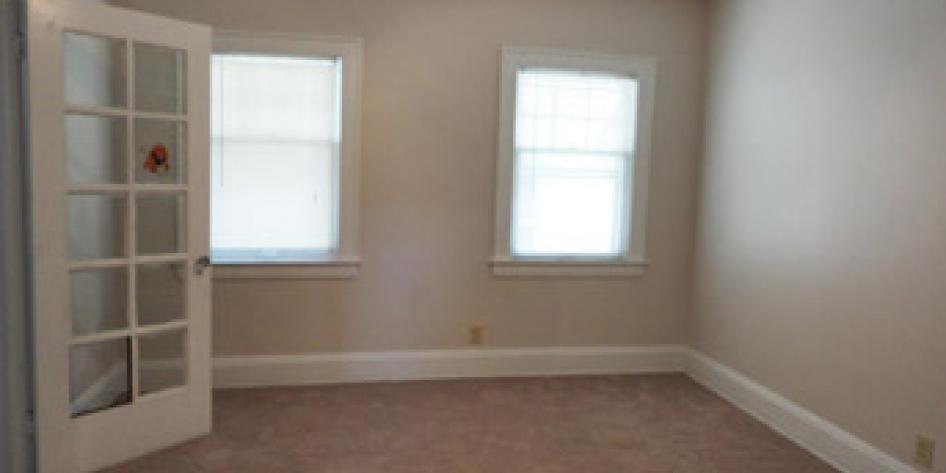 Creme colored bedroom with beige carpet and two large bright windows
