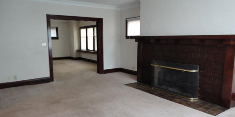 White living room with fireplace and beige carpet