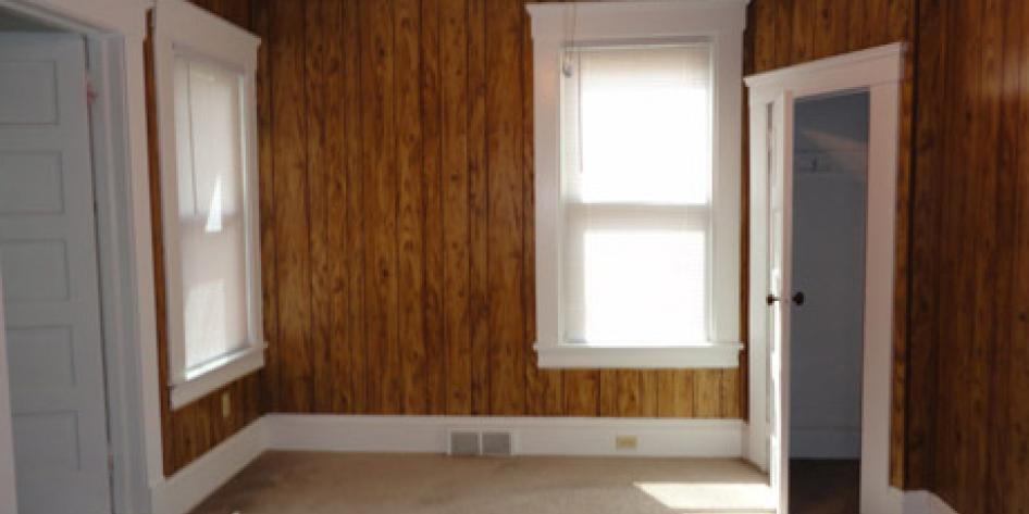 Brown, wood paneled wall bedroom with two bright windows and beige carpet