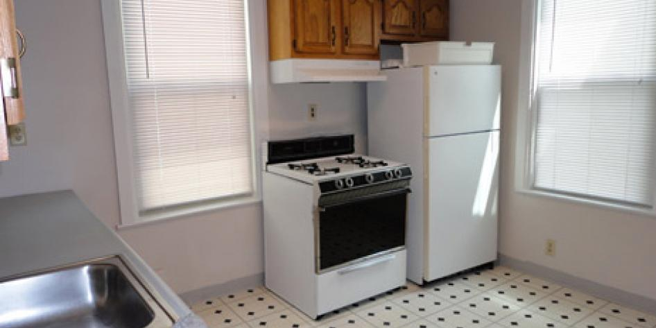 White kitchen with wood cabinets, refrigerator, stove and steel sink, with two bright windows