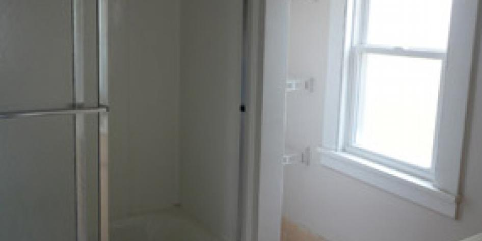 White bathroom with shower and bright window