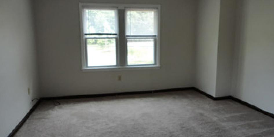 White carpeted living room with four bright windows