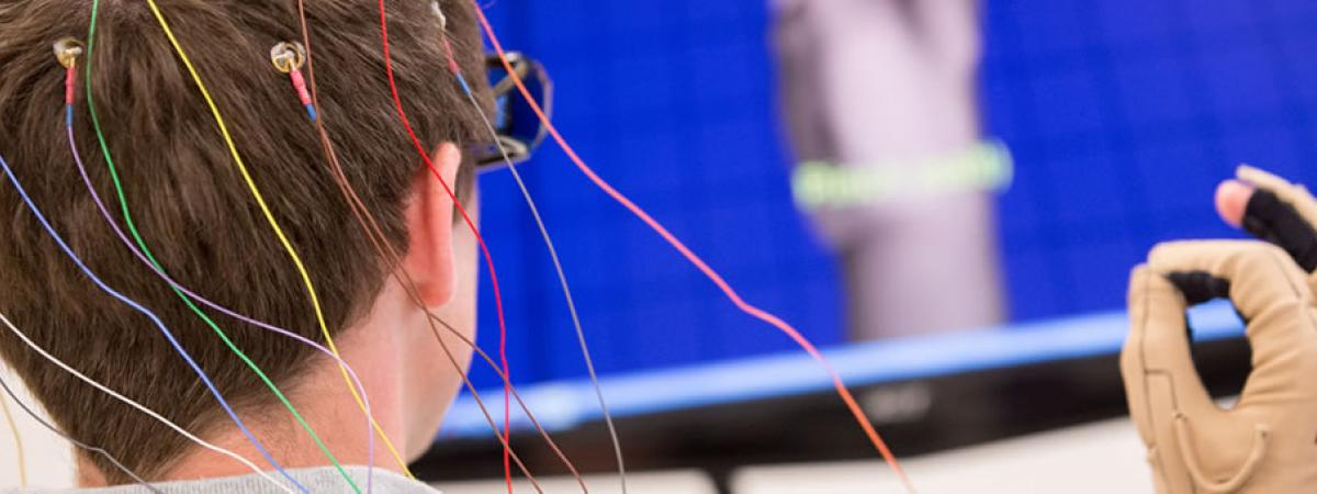 Picture of test subject with colored wires attached to his head with a special glove that connects to a computer display in the background