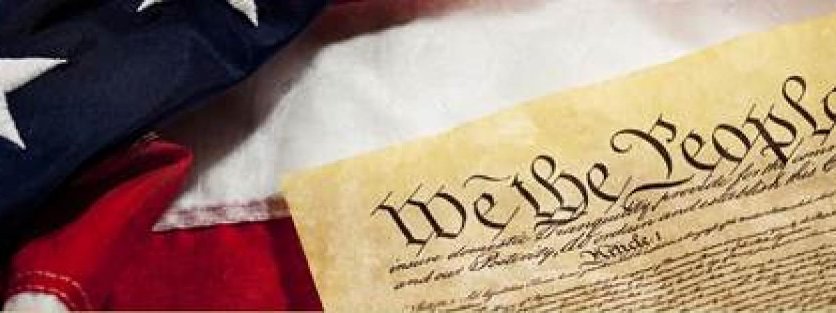 The united states flag and a copy of the constitution laying on it