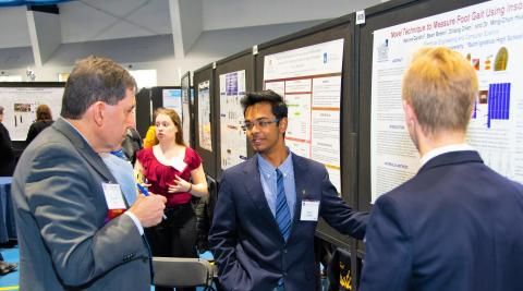 Dr. Donald Feke, CWRU Vice Provost for Undergraduate Education, listens as two students from Saint Ignatius High School present their research poster.
