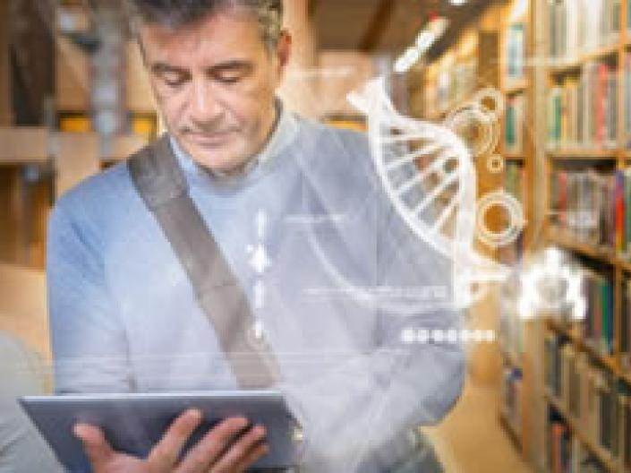 Picture of person next to a library shelf looking to mobile pad with scientific designs floating in the foreground