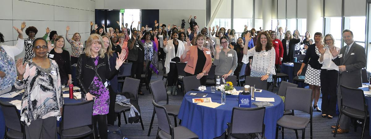 Participants of 2018 Admin Professionals Network Conference waving at camera.
