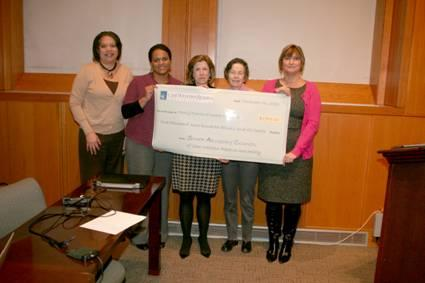 Members of the Case Western Reserve University Staff Advisory Council and representatives from Family Promise holding a check