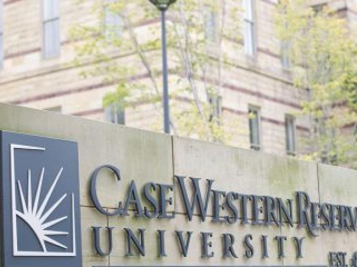 Case Western Reserve University logo appears on stone wall in front of Adelbert Hall.