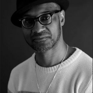 Photograph of Daniel Gray Kontar, a Black man wearing glasses and a hat, looking into the camera