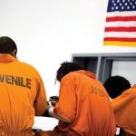 Young men in orange prison jumpsuits sitting with in a detention facility with their backs to the camera - an American flag hangs above them.
