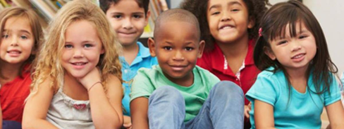 Photo of young children of various racial and gender identities smiling at the camera