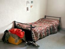 Photograph from Prison Nation exhibit depicting a stark bedroom scene