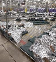 Photograph of immigrant detention center with wire fence and children sleeping on the floor