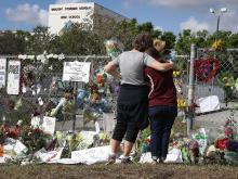 Photograph of mourners outside Marjory Stoneman Douglas High School in Parkland Florida following the shooting