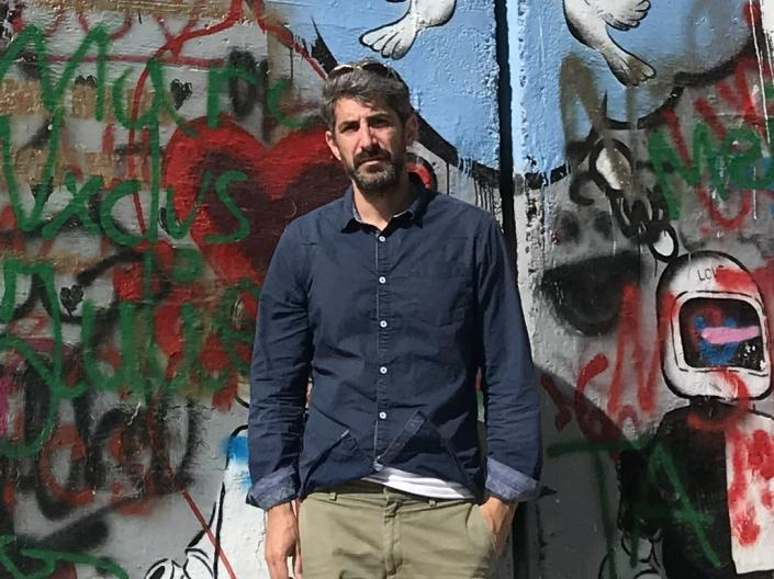 Photograph of Professor Avi Cover standing in front of the wall with grafitti between Israel and Gaza