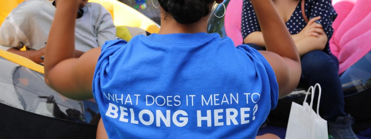 Woman standing with her back to us wearing shirt with saying What does it mean to belong here