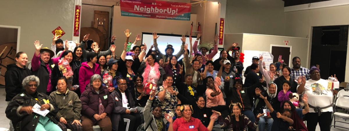 Large group of people with arms in the air under a sign reading NeighborUp