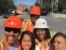 Group of 5 people wearing construction outfits smiling at the camera