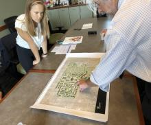 Man pointing at large map on table while young woman looks on.