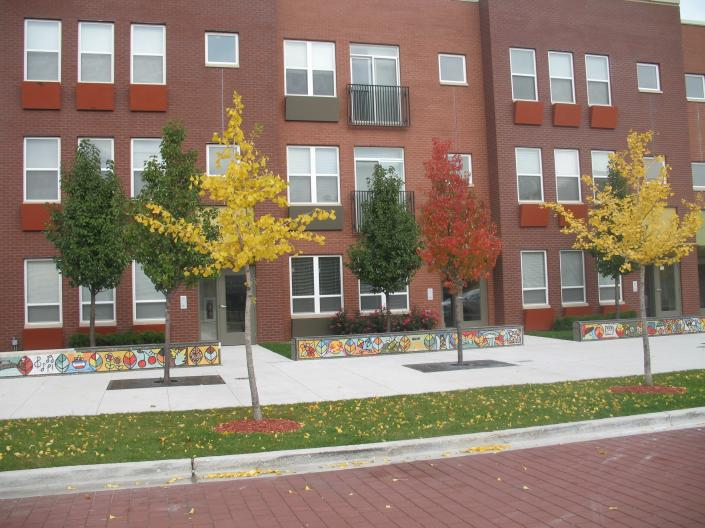 New red brick apartment building, trees in front with fall leaves