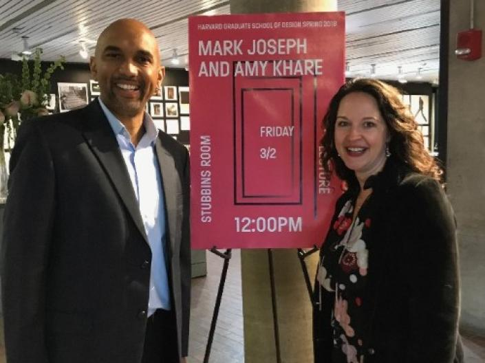 Mark Joseph and Amy Khare  standing in front of a sign