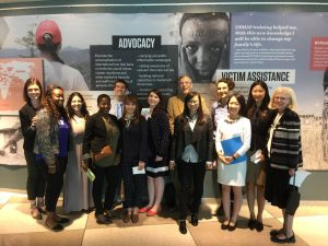Image of thriteen MSASS students and staff at United Nations, in front of large poster with the text advocacy and victim assistance, with unreadble text, a map on the right left side, and two images, one of women with back turned, and one of face of person in distress with head in hands