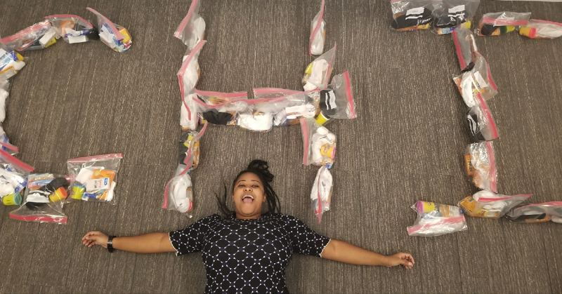 Young woman laying on her back on the floor. Above her are the letter CHI made from bags.