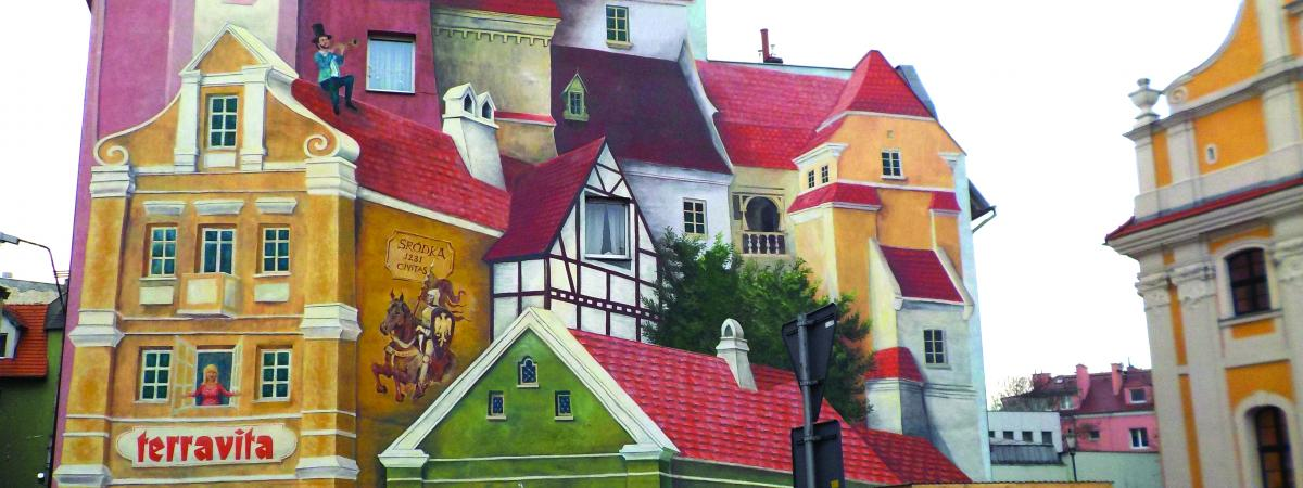 Image of large wall painted to depict many types of houses in red, yellow, green and white, with a sign titled, terravita, a woman looking out a window, an trumpet player with a top hat on a roof, a knight with a shield on a horse with title, srodka 1231 civitas, and baker looking out a doorway