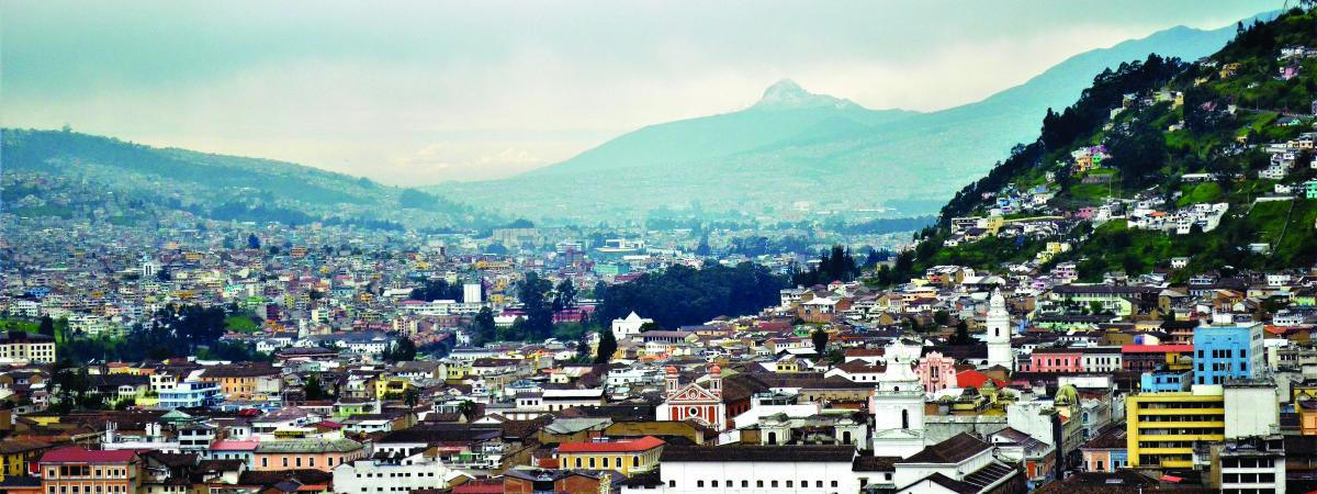 Image of landscape of Quito, Ecuador, with village in foreground and mountains and clouds in background