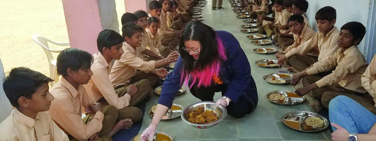 Student serving dinner in India
