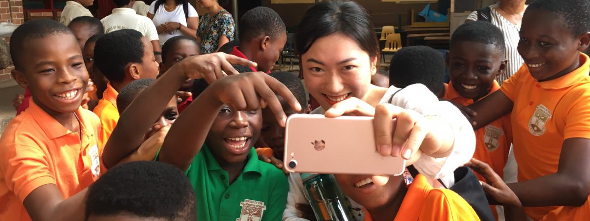 Social work student takes a selfie with a group of students in Ghana