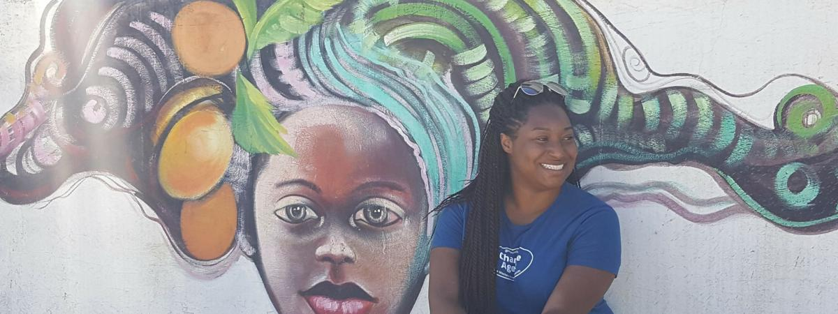 Woman sitting in front of mural