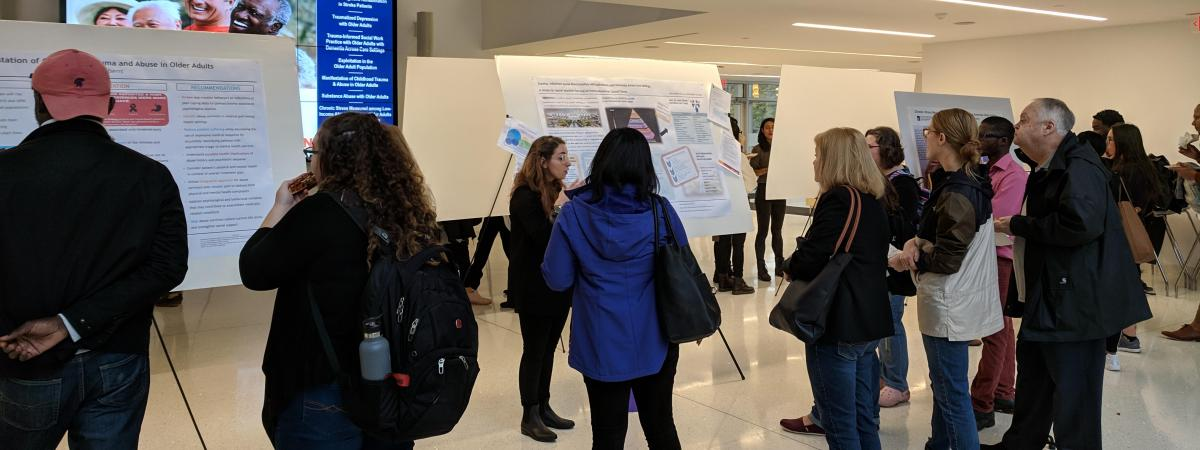 A social work student stands by their research poster and discusses work with a group