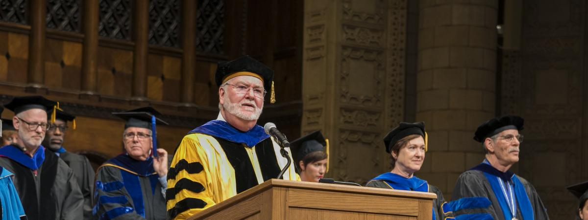 Dean Gilmore giving commencement speech at podium