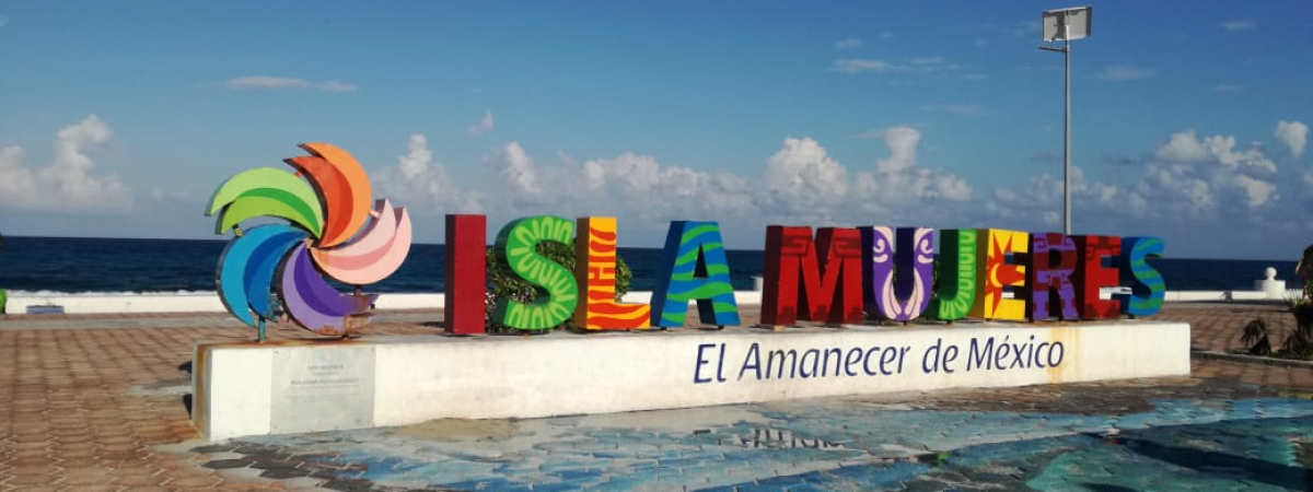 Colorful sign for Isla Mujeres on beach