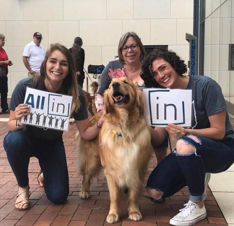 Social work students pose with a dog while holding All In signs on the steps of the Mandel School