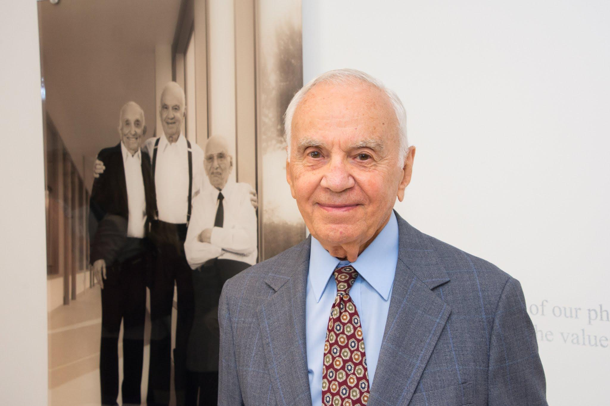 Morton Mandel standing in front of photo of him and his brothers