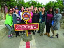 "Image of Case Western Reserve University students in Ecuador, on a road standing behind a sign reading ""Ecuador in the middle of the world Latitude: 00, 00, 00, calculated with gps"