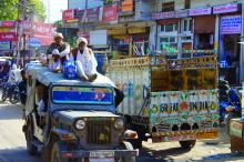 Image of two older en in traditional white indian dress on top of a jeep with many others inside, traversing a busy urban road, passing another truck with wooden sides, painted white with advertisements, on street with many shops and signs