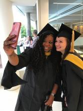 Female students in cap and gown taking a selfie