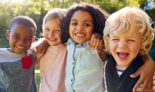 Group of diverse children hugging and laughing