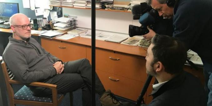 Image of Dr. Daniel J. Flannery being interviewed by News 5 Cleveland, sitting in chair in his office on left of image, with reporter and cameraman on right