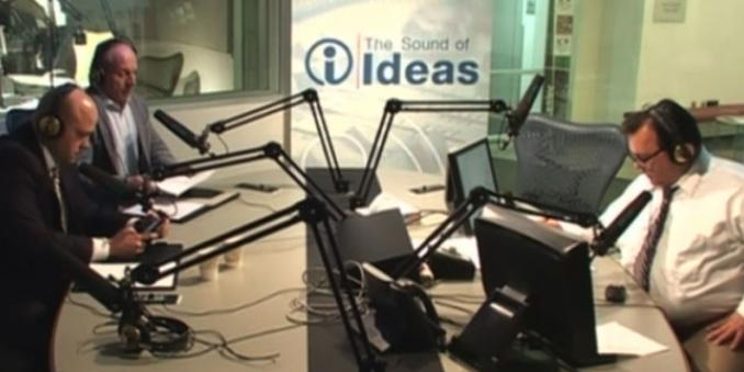 Image of interview with Daniel J. Flannery, with two people sitting on right side in recording booth, and one person on left, all with headphones and microphones, with a banner behind with text the sound of ideas, with letter i within a circle, all in blue against a white background