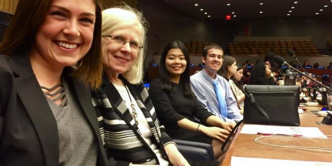 MSASS students and faculty at United Nations, smiling and sitting behind a very long wooden desk within a very large room