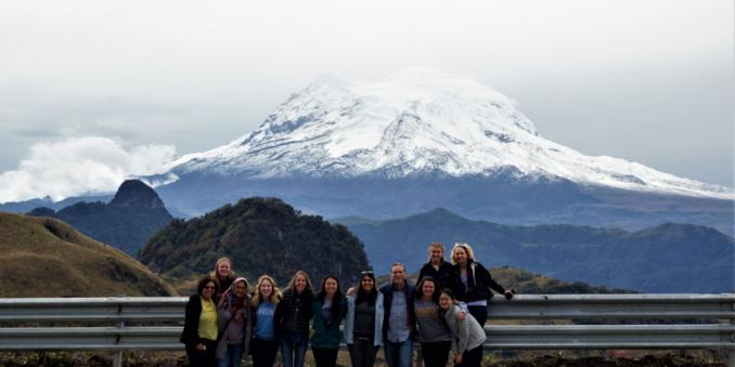Image of 12 MSASS students in front of snow-capped mountain in India