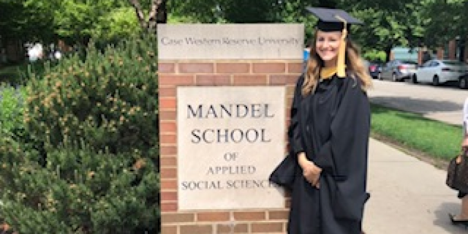 Rachel Truhan in graduation cap and gown standing in front of a sign for the Mandel School of Applied Social Sciences