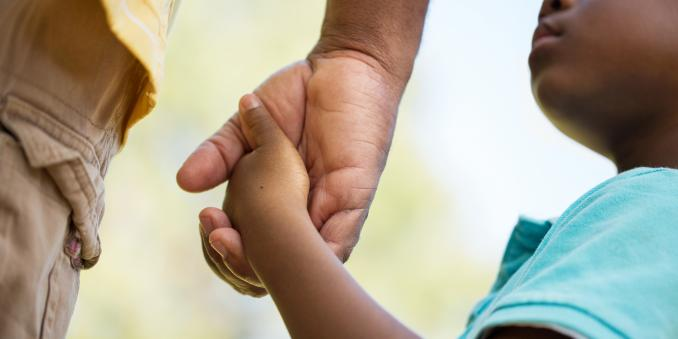 Black child holding an adult's hand